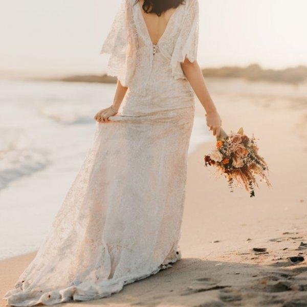 Невеста на берегу с осенним свадебным букетом