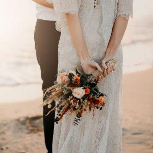 Рустикальный осенний свадебный букет из роз и сухоцветов держит невеста