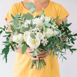 Белый букет невесты Растрёпыш из белых цветов с зеленью в руках у девушки
