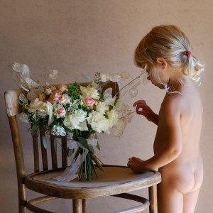 Бело-розовый букет невесты с сухоцветами изучает ребенок