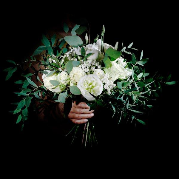 Белый букет невесты растрепыш из белых цветов с зеленью в руке в темноте
