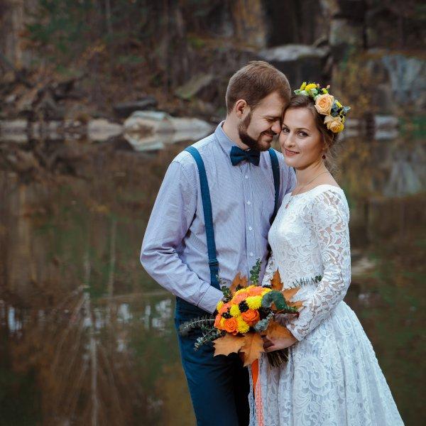 Молодожены, невеста с осенним букетом и венком из живых цветов в волосах