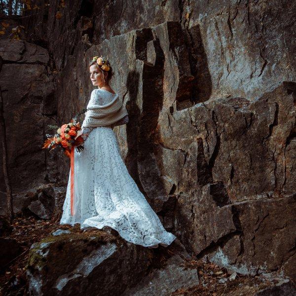 Хрупкая невеста в осеннем образе на фоне гранитной стены