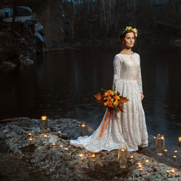 Нежная невеста с желто-оранжевым букетом в окружении свечей