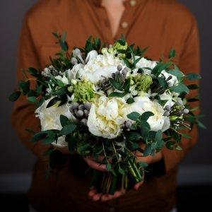 Бело-зеленый букет невесты с пионами держит флорист Pion Bouton