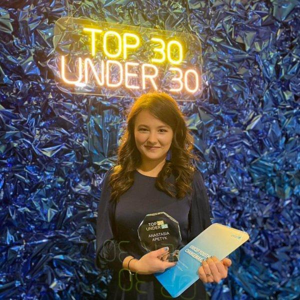 Победительница Top30 Under30 на фоне синей фотозоны