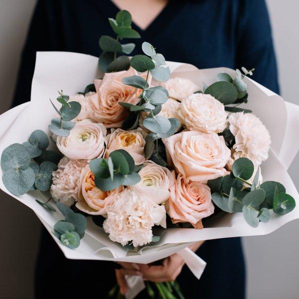 Букет из роз, ранункуюсов, гвоздик и эвкалипта держит девушка