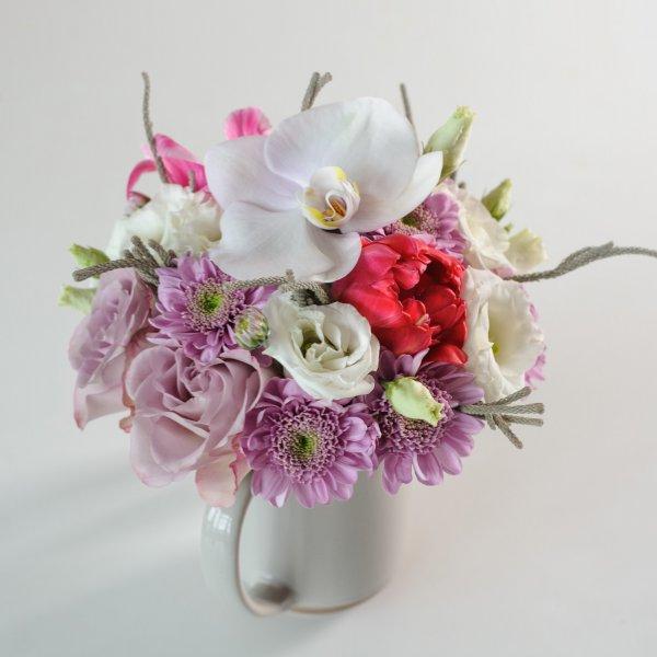 Центральное место в букете в чашке занимает белая орхидея