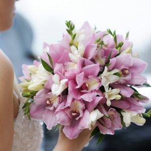 Стильный букет из орхидеи и фрезии в руке невесты