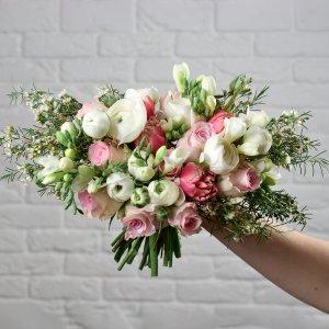 Слегка растрепанный нежный букет невесты из роз, ранункулюсов и хамелациума