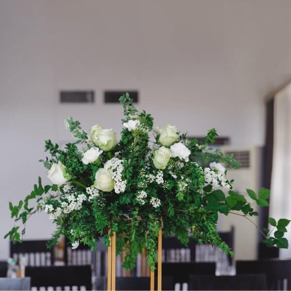 Композиция из зелени с белыми цветами для стола гостей на вершине золотой подставки