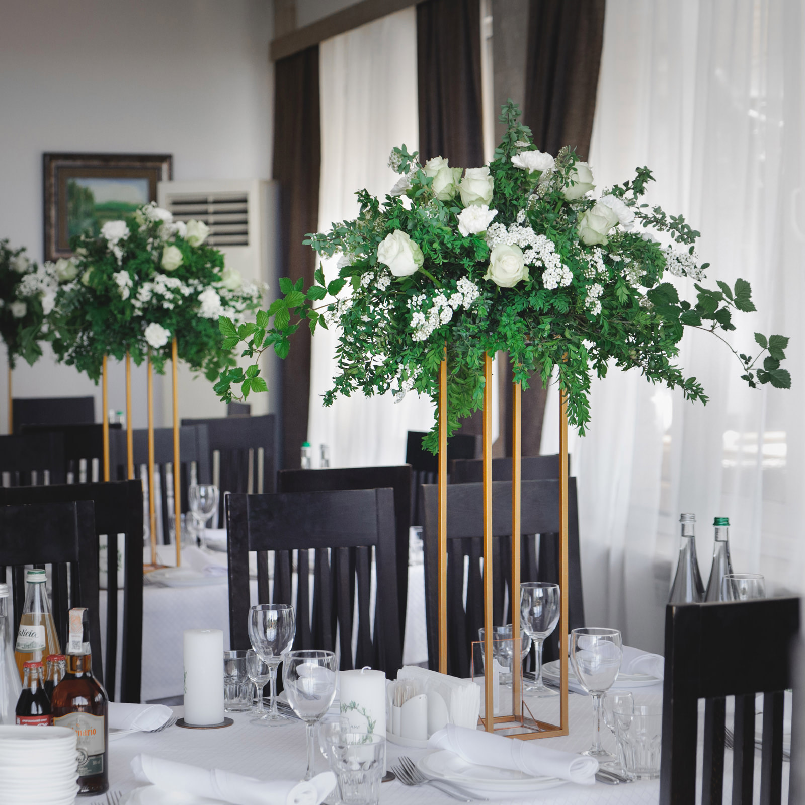 Композиция из зелени с белыми цветами на столах гостей в зале ресторана