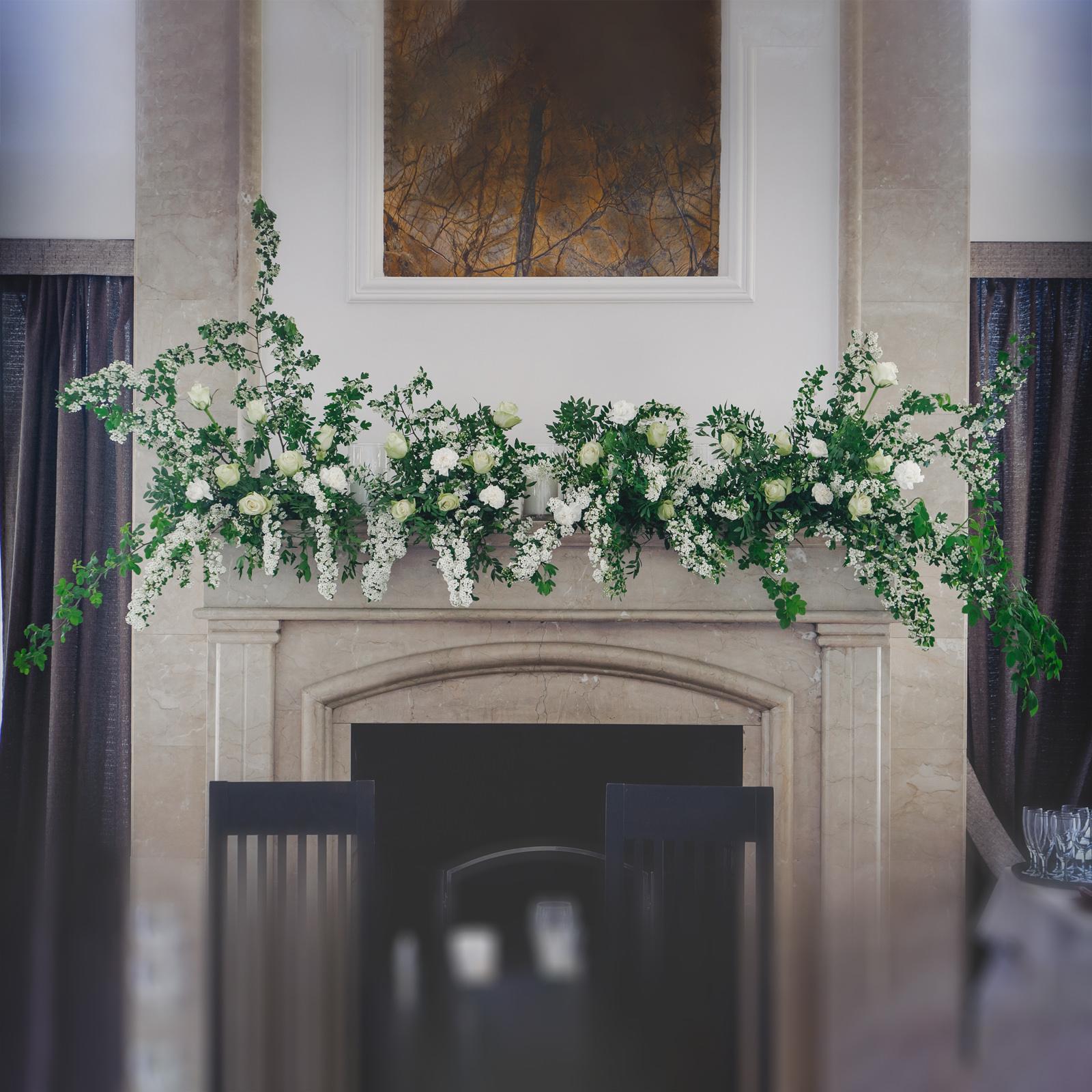 Карниз камина украшен цветочной композицией с свечами