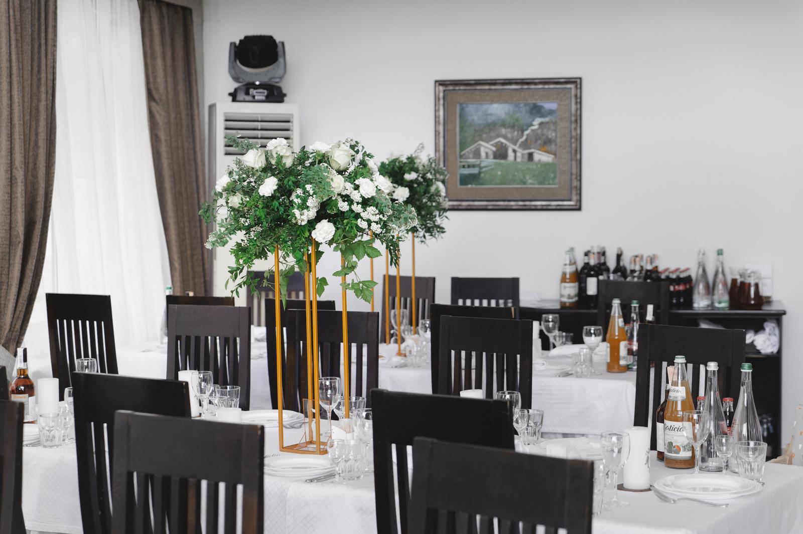 Банкетные столы зала ресторана украшенный к свадьбе