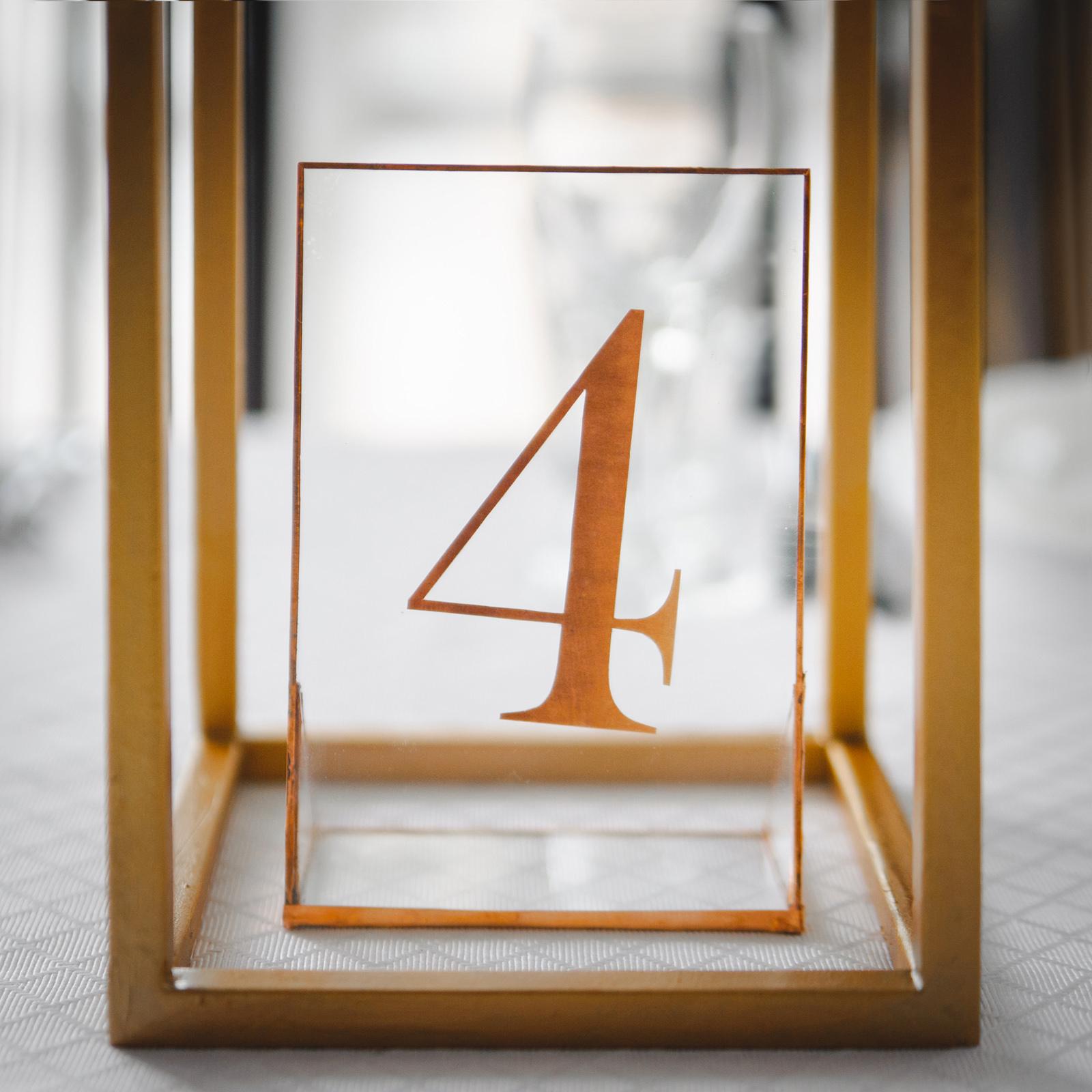 Нумерация столов гостей выполнена в виде номерка на прозрачной подставке поставленного в основание подставки для цветов