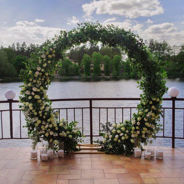 Круглая свадебная арка из зелени и цветов на террасе ресторана с выходом на озеро